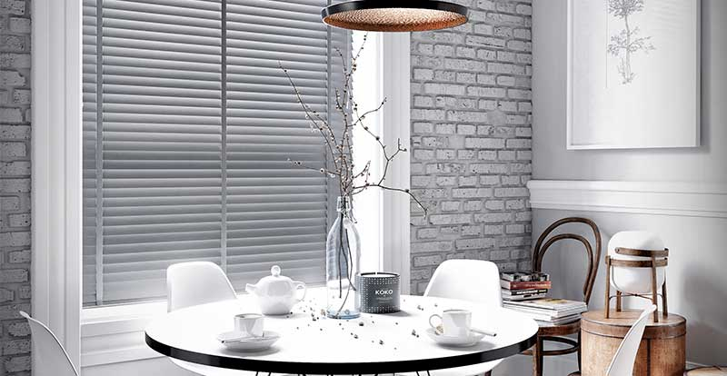 A grey faux wooden blind in a dining room