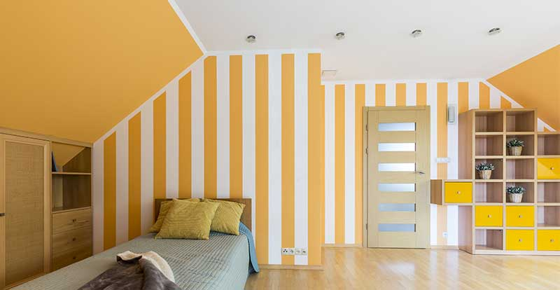 Yellow striped feature wall in a bedroom