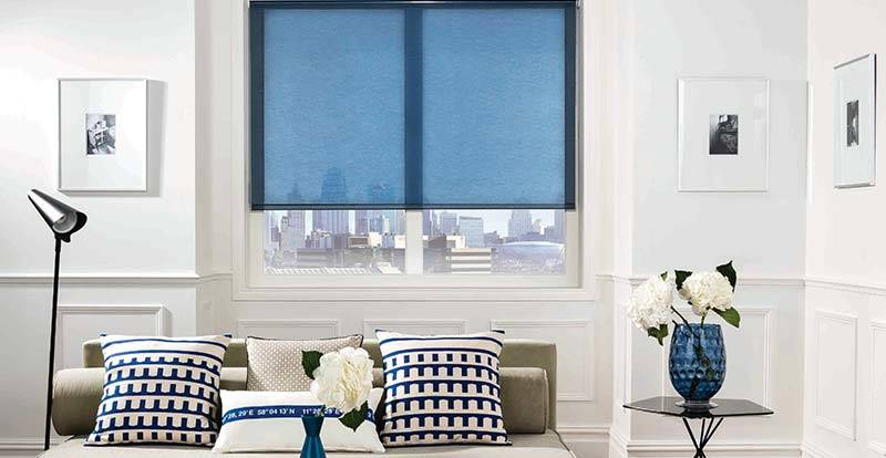 Blue solar control voile roller blind in a living room window