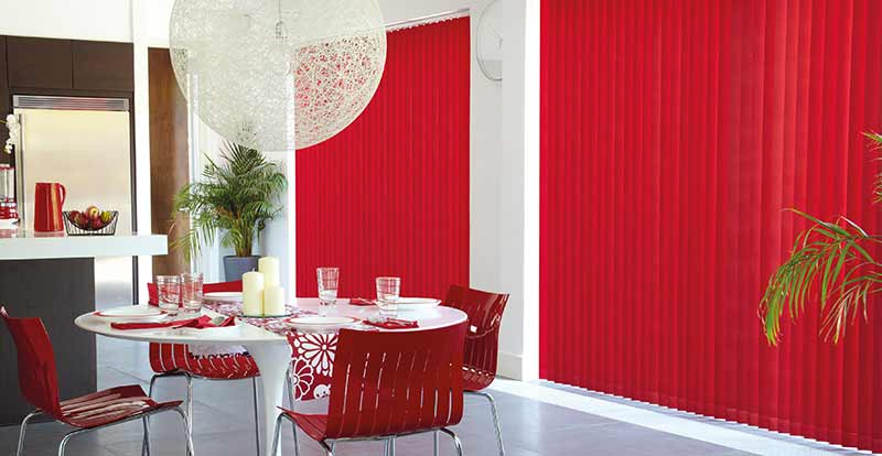 Red vertical blinds in a dining room.
