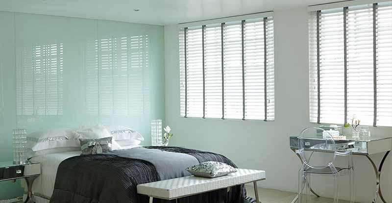 White taped wooden blinds in a bedroom