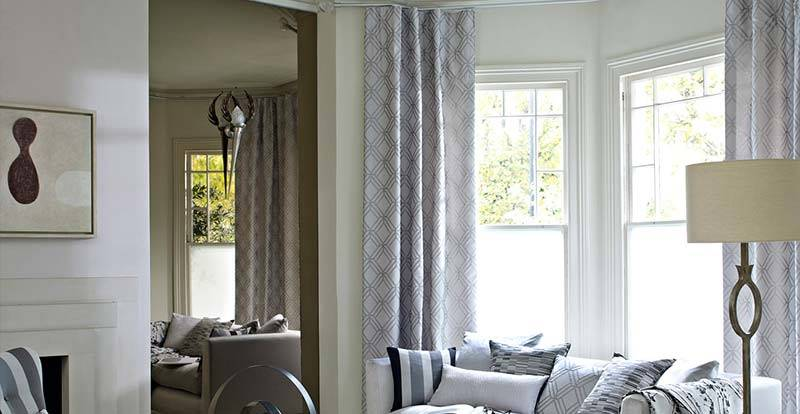 Grey full length curtains in a living room.