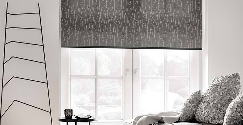 Close up of a living room window with a grey patterned roller blind blocking sunlight