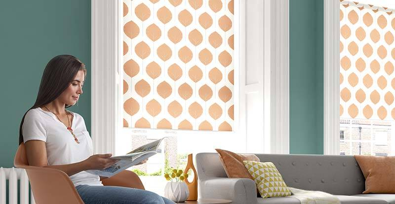 Lady reading a magazine in a bright living room with a patterned orange roller blind
