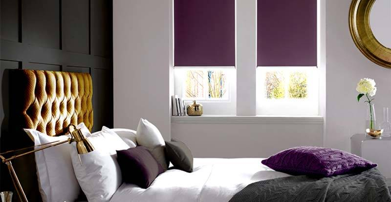 Purple blackout electric roller blind in a bedroom