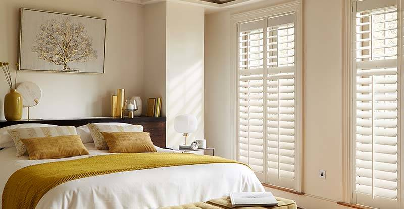 Bedroom with white real wood full height shutters
