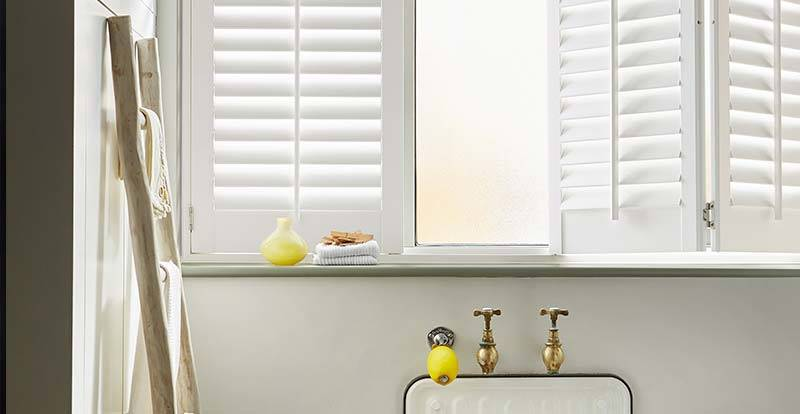 Close up of white faux wood full height shutters in bathroom