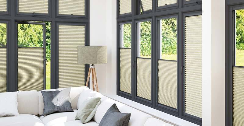 Cream blackout perfect fit pleated blinds in a conservatory.