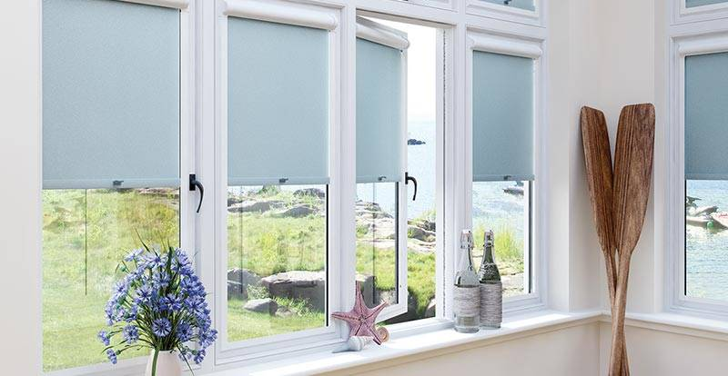 Blue Perfect Fit Roller Blinds in a set of windows