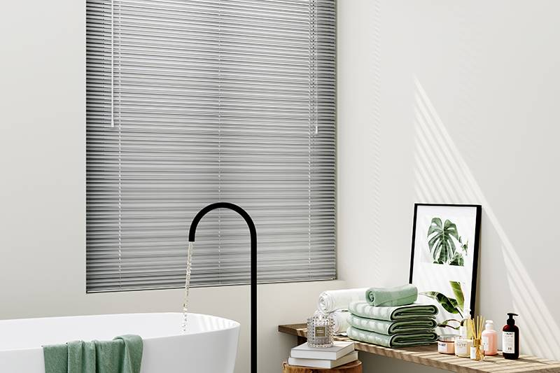 Grey aluminum venetian blind in a large bathroom window