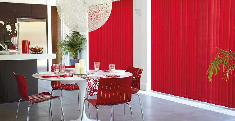 Red vertical blinds with chainless weights in a kitchen