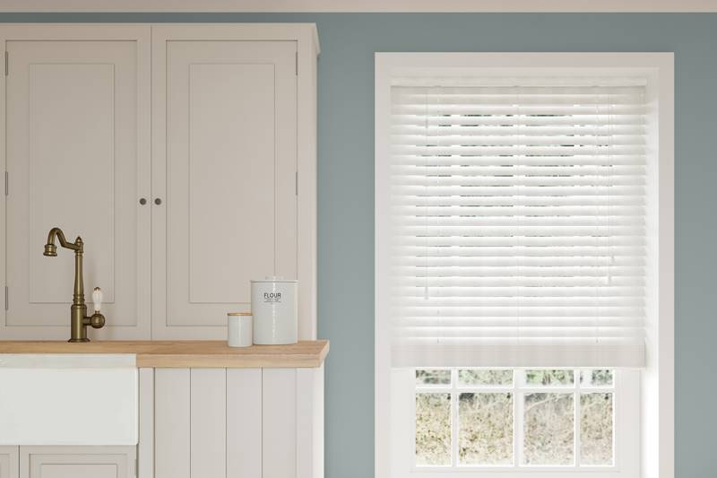 White faux wood blind in a large kitchen window