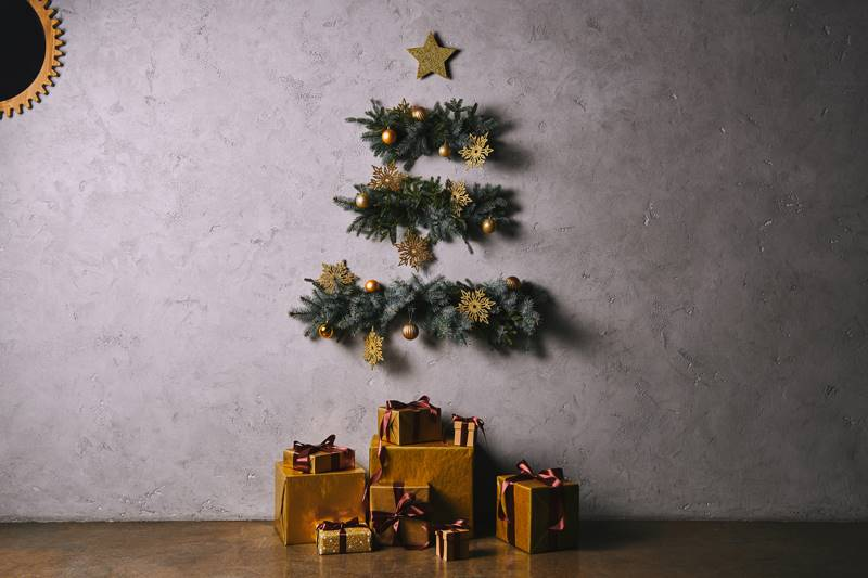 Handmade Christmas tree hanging on grey wall, gift boxes on floor in room