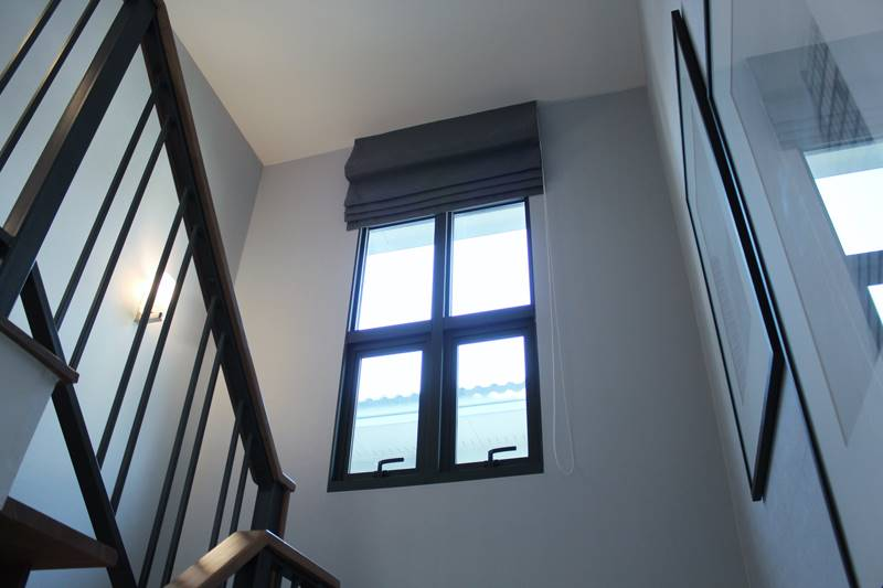 Grey roman blind in a large staircase window