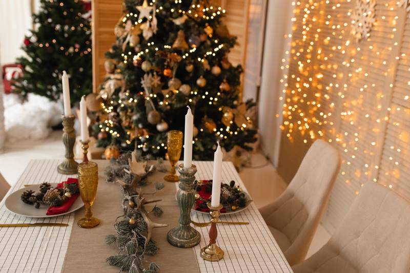 Served table with Christmas decor and bokeh lights background, candles and Christmas tree.