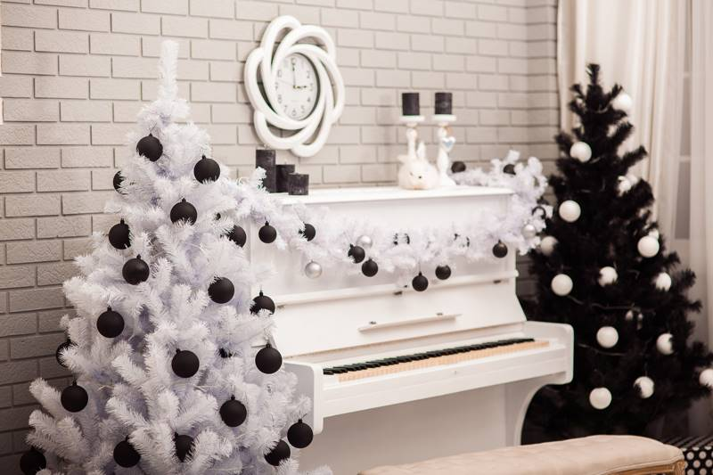 Black and White Christmas tree near white piano at the gray brick wall background.