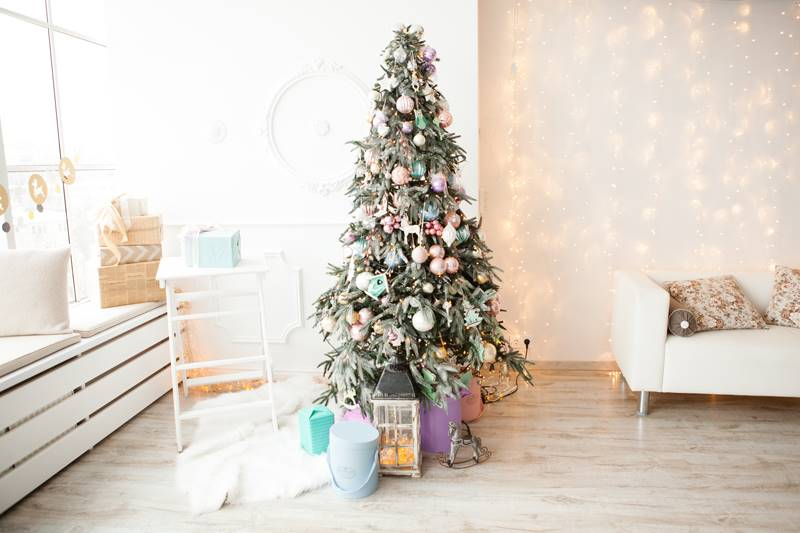 Christmas tree decorated with glass and wooden vintage toys and gift boxes in pastel colors.