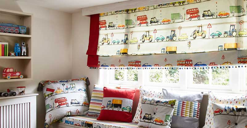 Patterned light filtering roman blind in a playroom