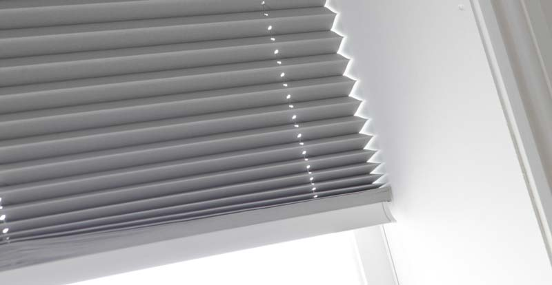 Close up of a grey neat fit pleated blind